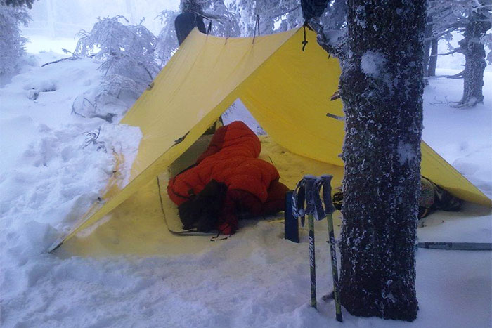 Pavel nestled under his SuperLight Tarp on a snowboarding expedition in Czech Republic
