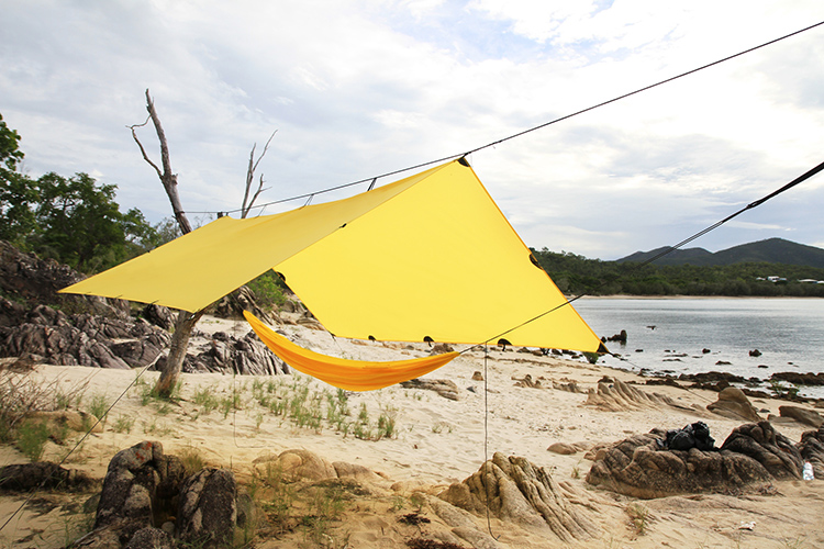 DD Superlight tarp bright yellow set up with superlight hammock on the beach